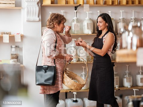A senior woman smelling an eco-friendly product on her arm at the sustainable store.