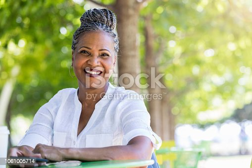 istock Senior woman smiles at the camera while sitting in quiet park 1061005714