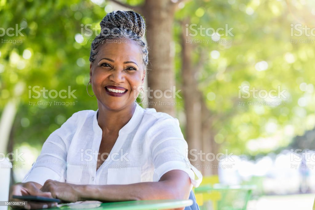 Senior woman smiles at the camera while sitting in quiet park stock photo