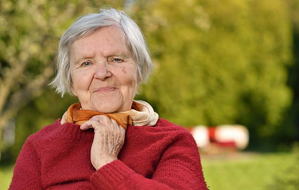 Senior woman smiling and dreaming in garden. stock photo