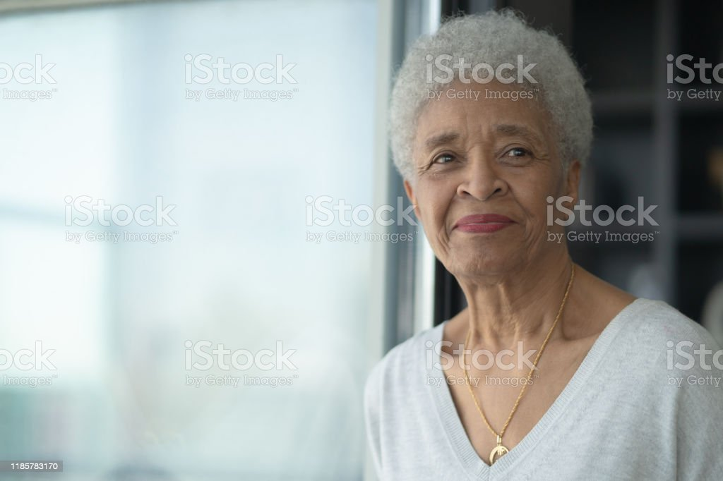 A Senior Woman Smiling As She Reflects stock photo A senior African woman sits beside a window and gazes off into the room as she is deep in thought and reflection.  She has a gentle smile on her face and is wearing a casual and comfortable sweater in this head shot. 50-54 Years Stock Photo