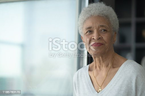 A senior African woman sits beside a window and gazes off into the room as she is deep in thought and reflection.  She has a gentle smile on her face and is wearing a casual and comfortable sweater in this head shot.
