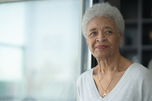 A Senior Woman Smiling As She Reflects Stock Photo Stock Photo - Download Image Now
