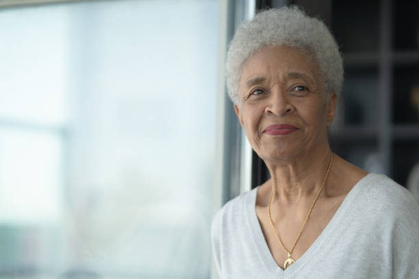 een senior vrouw glimlachend als ze stockfoto reflecteert - 50 59 jaar stockfoto's en -beelden