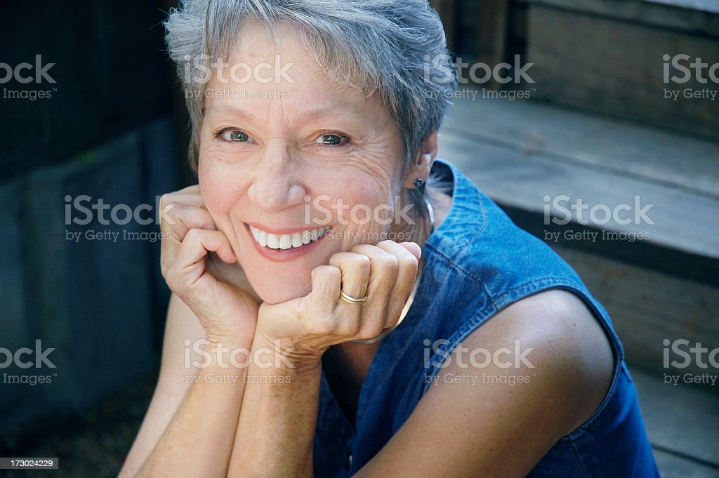 Senior woman smiling at the camera sitting in stairs royalty-free stock photo