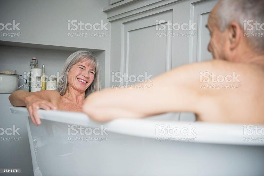 Mulher sênior sorrindo no banheiro com o marido em primeiro plano - foto de acervo