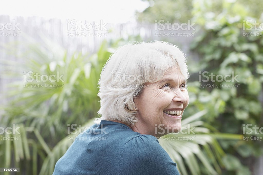 Senior woman smiling in garden royalty-free stock photo