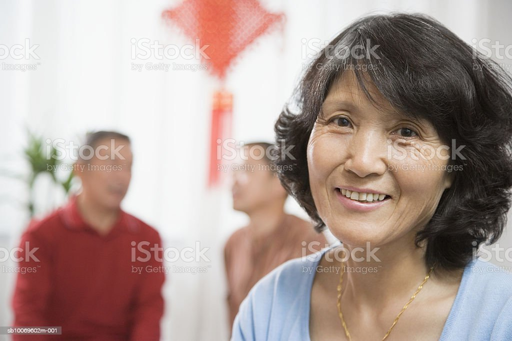 Senior woman smiling, men in background foto stock royalty-free