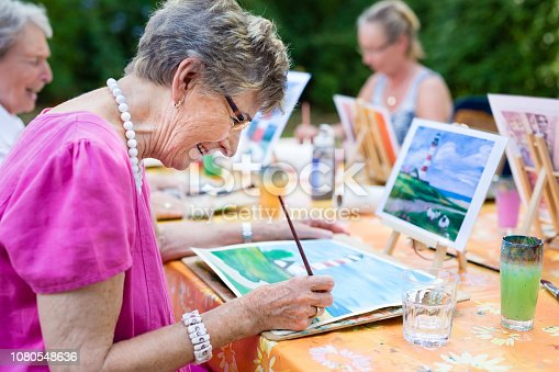 istock Senior woman smiling while drawing with the group. 1080548636