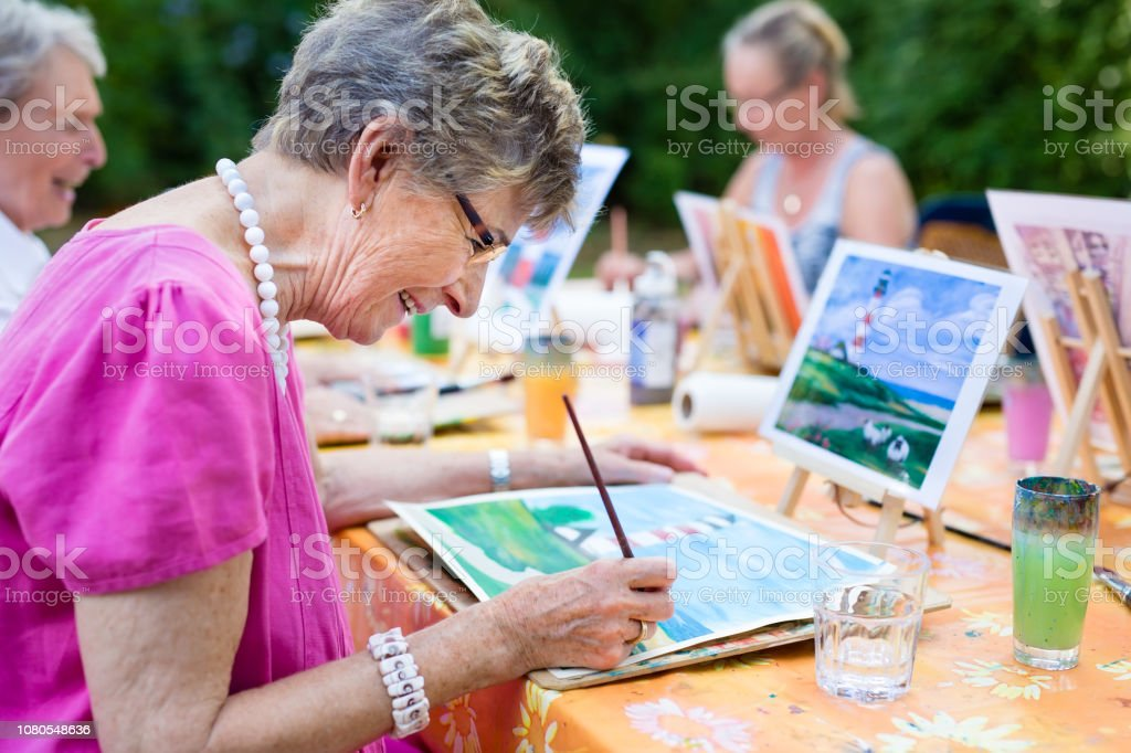 Senior woman smiling while drawing with the group. stock photo