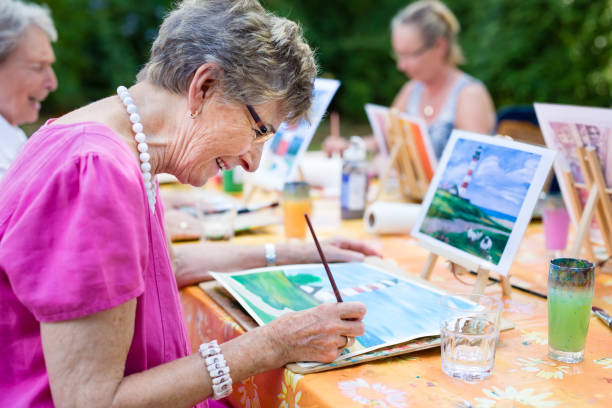 senior woman smiling while drawing with the group. - idosos imagens e fotografias de stock
