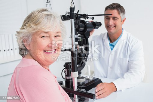 istock Senior woman smiling while sitting with optician 471562840