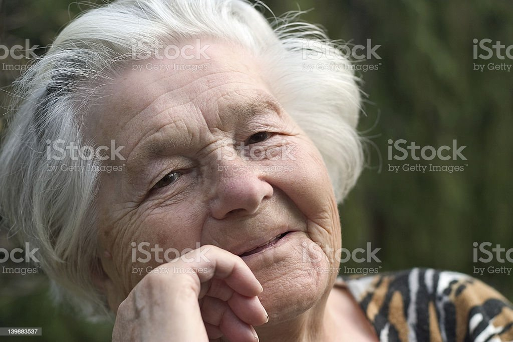 Senior woman smiling with a hand against her cheek royalty-free stock photo