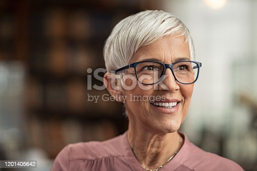 Portrait of smiling mature woman with spectacles and short grey hair in library looking away. Senior librarian standing in reading hall and thinking. Old beautiful lecturer contemplating in library. Future and vision concept.