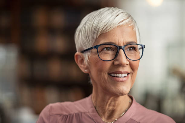 Senior woman smiling with eyeglasses Portrait of smiling mature woman with spectacles and short grey hair in library looking away. Senior librarian standing in reading hall and thinking. Old beautiful lecturer contemplating in library. Future and vision concept. looking away stock pictures, royalty-free photos & images