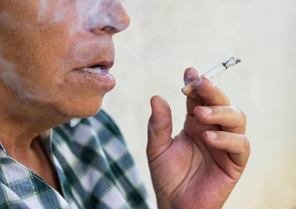 Senior woman smoke a cigarette stock photo