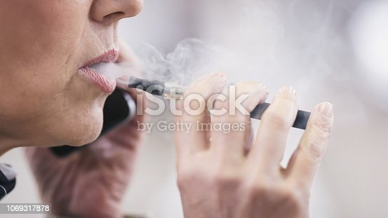 1047058184 istock photo Senior woman smoking electronic cigarette 1069317878