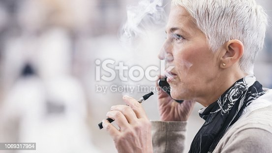 1047058184 istock photo Senior woman smoking electronic cigarette 1069317954