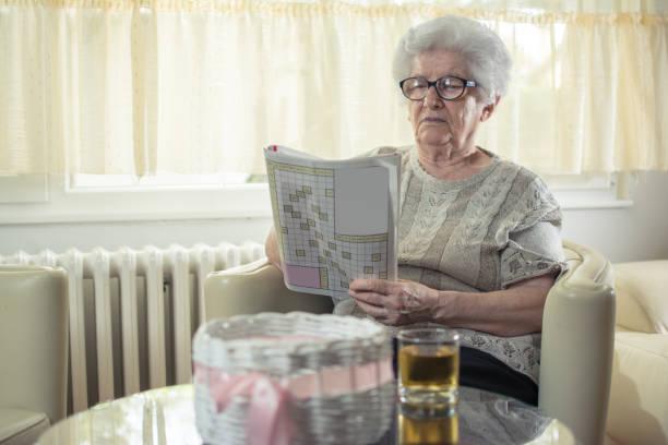 ältere frau zu hause ein kreuzworträtsel zu lösen. - kreuzworträtsel lexikon stock-fotos und bilder