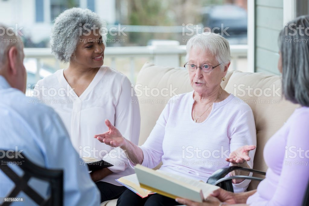 Senior woman speaks to fellow book club members stock photo