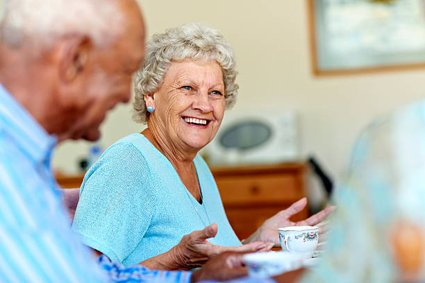 Senior woman spending leisure time with friends Happy senior woman spending leisure time with friends in nursing home retirement community stock pictures, royalty-free photos & images
