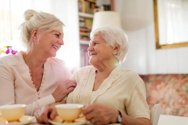 senior woman spending quality time with her daughter - filhos adultos imagens e fotografias de stock