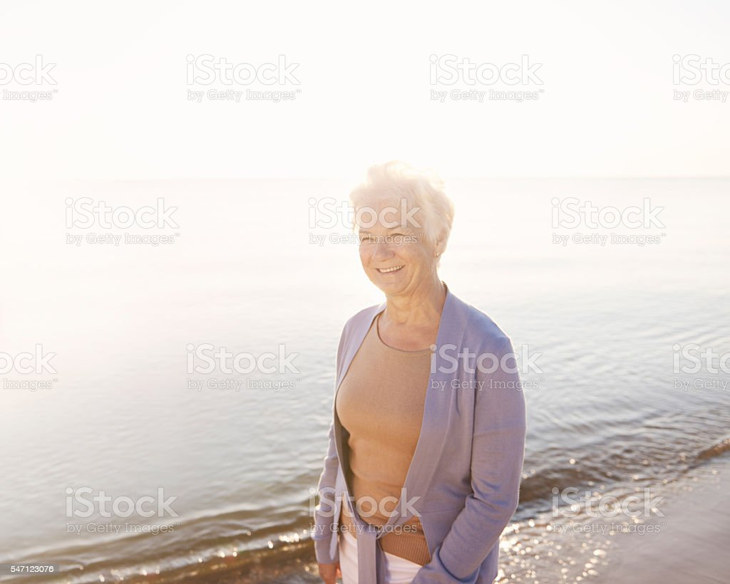 Senior woman spending time by the ocean stock photo