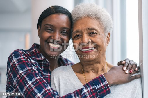 Portrait of a senior African American woman and her adult daughter. They are smiling while resting their foreheads against each other. They are looking out a window thoughtfully. The women are full of gratitude and hope for the future.