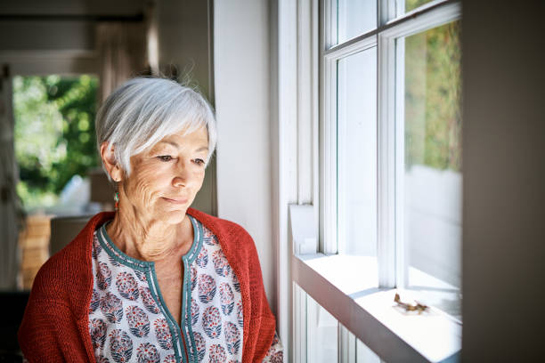 Senior woman standing alone at home lost in thought stock photo