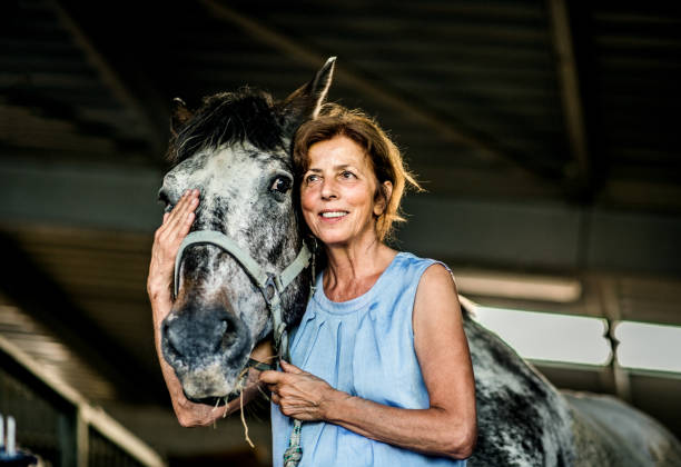 A senior woman standing close to a horse in a stable, holding it. A happy senior woman with closed eyes standing close to a horse in a stable, holding it. appaloosa stock pictures, royalty-free photos & images