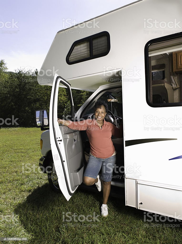 Senior woman standing in doorway of motorhome, smiling royalty-free stock photo