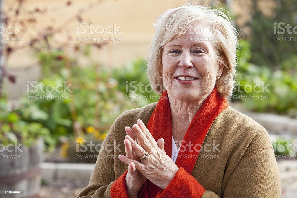Senior woman standing in garden stock photo
