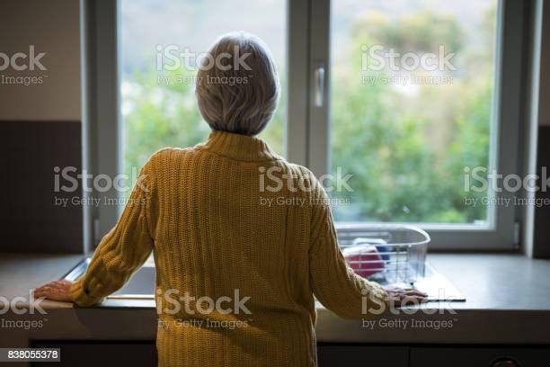 Senior woman standing near the kitchen sink and looking through picture id838055378?b=1&k=6&m=838055378&s=612x612&h=ahrwx7kob1xzjlp tttfoxs 13wvfvt pgynvpv0mfs=