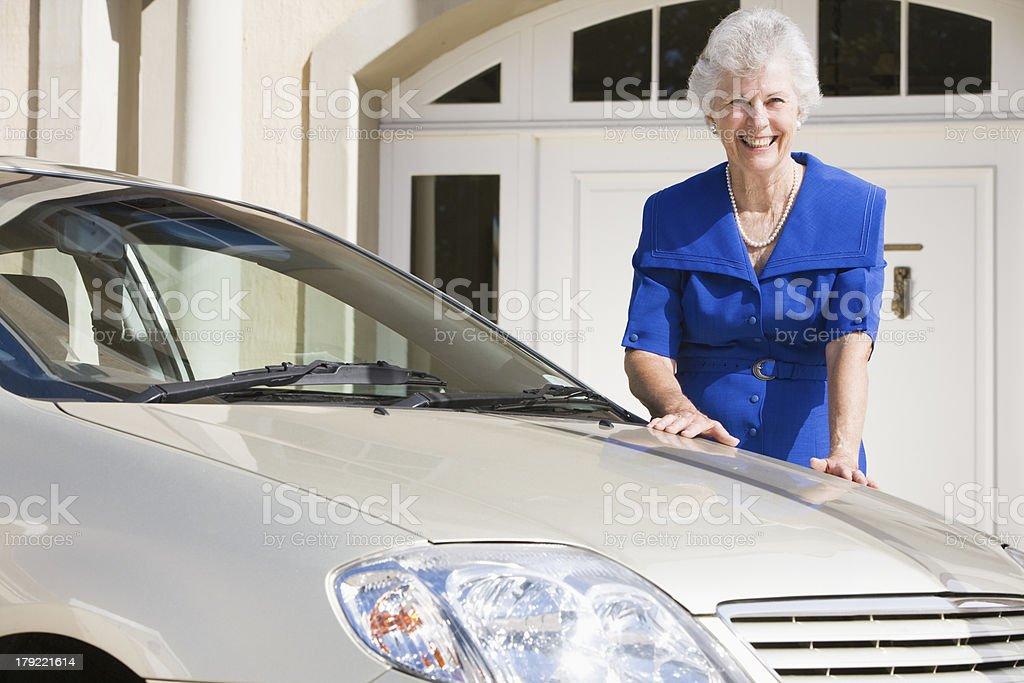 Senior woman standing next to new car royalty-free stock photo