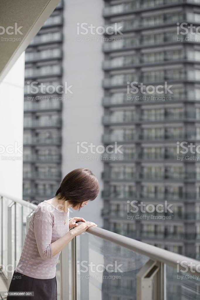 Senior woman standing on balcony looking down royalty free stockfoto