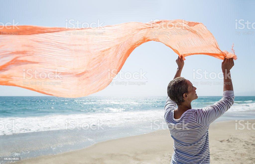 Senior Frau stehen am Strand halten Schal – Foto