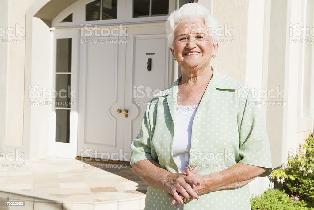 Senior woman standing outside house royalty-free stock photo