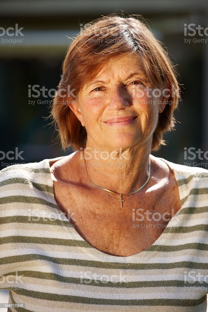 Senior woman standing, smiling over a blurred background stock photo