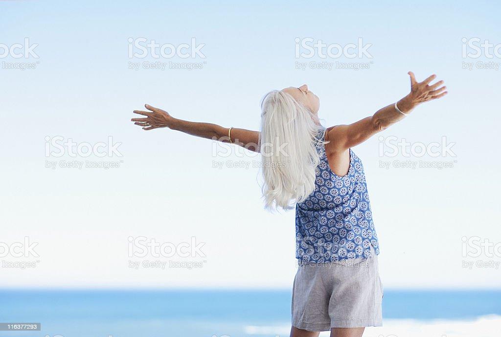 Senior Frau stehend mit Ausgestreckte Arme am Strand – Foto