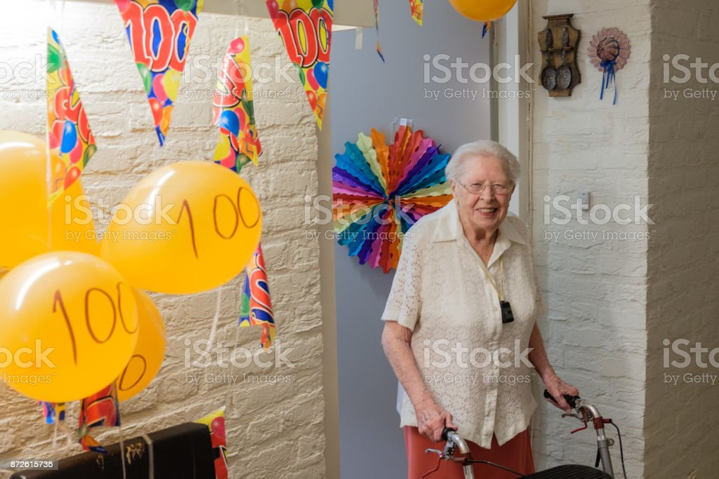 senior woman stands in front of her decorated room door celebrating her 100th birthday stock photo