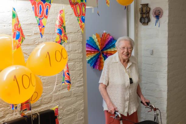 ältere frau steht vor ihrer eingerichteten zimmertür feiert ihren 100. geburtstag - nummer 100 stock-fotos und bilder