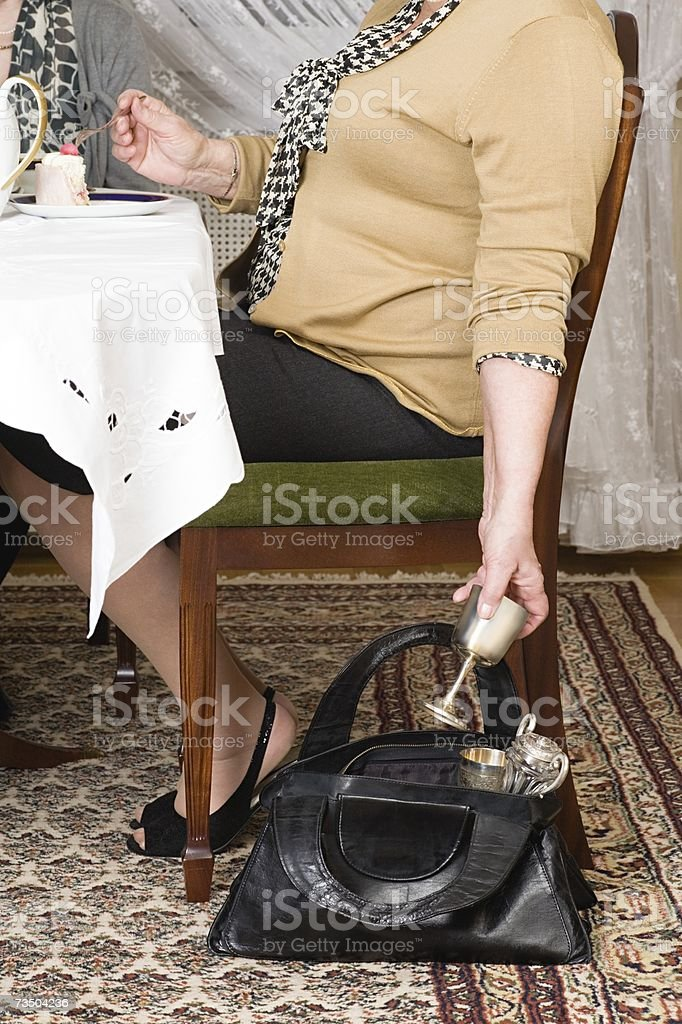 Senior woman stealing a goblet royalty-free stock photo