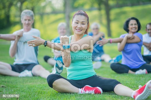 istock Senior Woman Stretches With Group 801309780