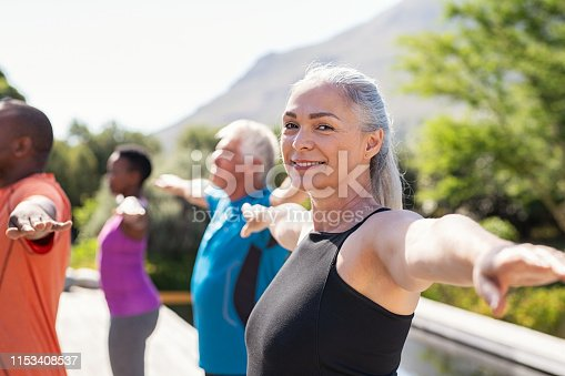 istock Senior woman stretching arms in yoga class 1153408537