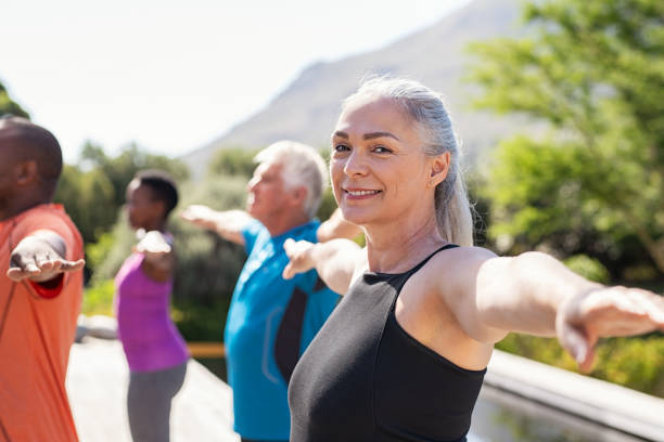 femme aîné étirant des bras dans la classe de yoga - femme et energie photos et images de collection