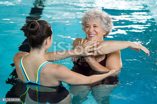 612839448istockphoto Senior woman stretching in pool 612839056