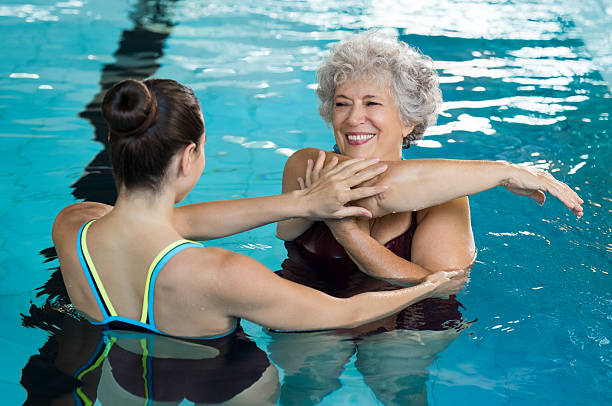 Senior woman stretching in pool Young trainer helping senior woman in aqua aerobics. Senior retired woman staying fit by aqua aerobics in swimming pool. Happy old woman stretching in swimming pool with young trainer. alternative therapy stock pictures, royalty-free photos & images