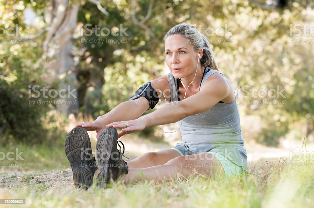 Senior woman stretching stock photo