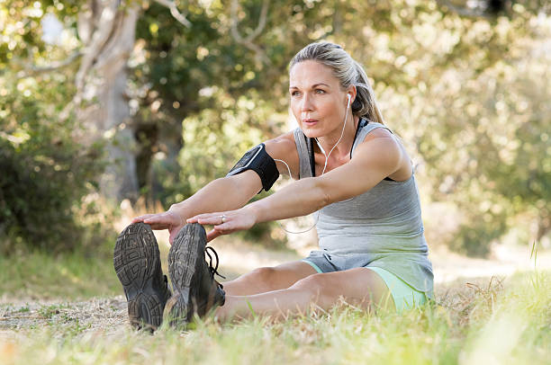 Senior woman stretching Senior woman exercising in park while listening to music. Senior woman doing her stretches outdoor. Athletic mature woman stretching after a good workout session. touching toes stock pictures, royalty-free photos & images