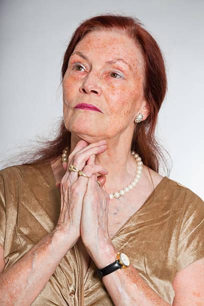 Senior woman studio shot against grey background stock photo